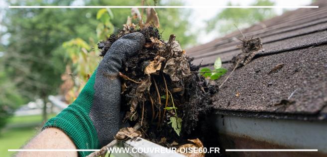 homme nettoyant une gouttiere avec terre et feuilles
